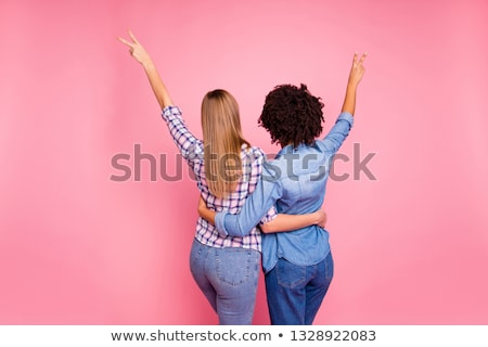 Stock photo: Girl shows a sign of victory behind her back