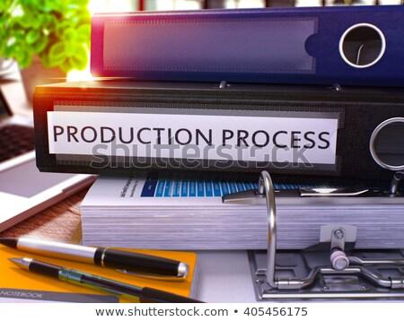 Production Process on Black Ring Binder. Blurred, Toned Image. Stock photo © tashatuvango