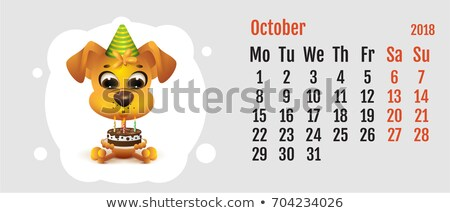 2018 year of yellow dog on chinese calendar fun dog holding cake calendar grid month october stock photo © orensila