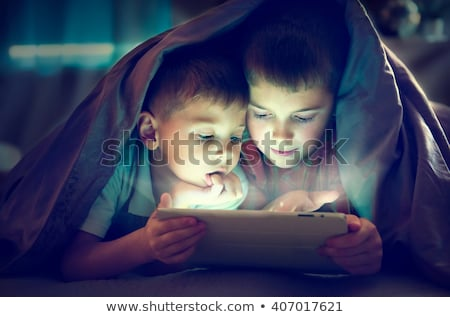 kid using tablet in darkness bedroom stock photo © vinnstock