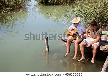 Two men sit chatting on lake jetty Stock photo © IS2
