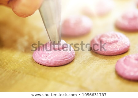 chef with injector squeezing macaron batter Stock photo © dolgachov