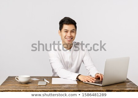 asian man sitting at office desk with computer stock photo © studioworkstock