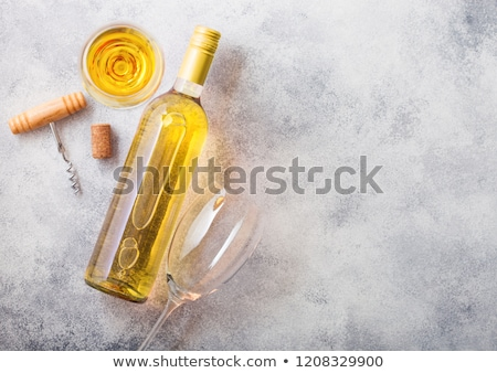 Bottle and glasses of white wine with cork and crkscrew opener on stone kitchen table background. To Stock photo © DenisMArt