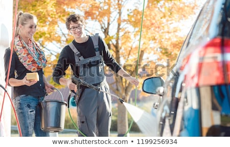 Service man helping woman cleaning her auto in car wash Stock photo © Kzenon