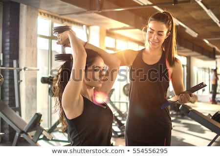 Woman exercise in a gym with the help of her personal trainer Stock photo © boggy