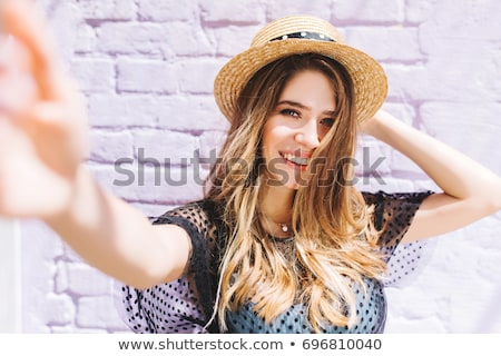 Fashionable ladies with hairstyle taking selfie outdoors. Stock photo © studiolucky