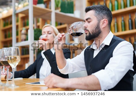 Young male sommelier smelling red wine in bokal Stock photo © pressmaster