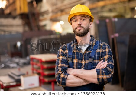 Young bearded foreman in overalls and hardhat crossing arms by chest Stock photo © pressmaster