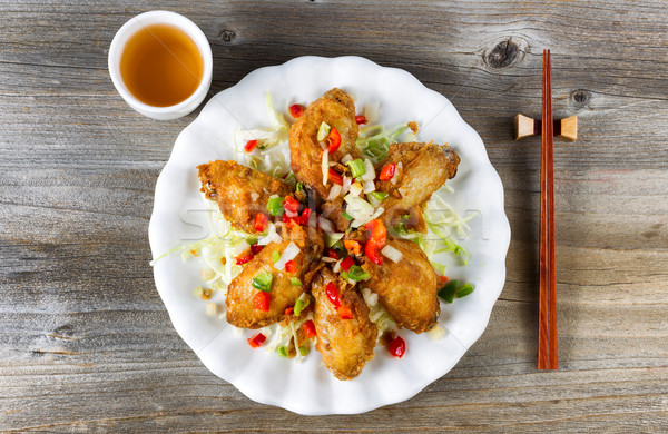Asian style chicken wings with tea in white plate on rustic wood Stock photo © tab62