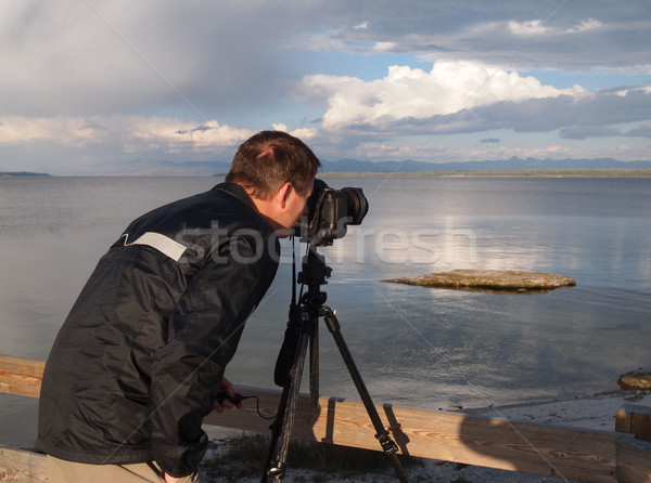 Man taking photo of lake with camera mounted on tripod Stock photo © tab62