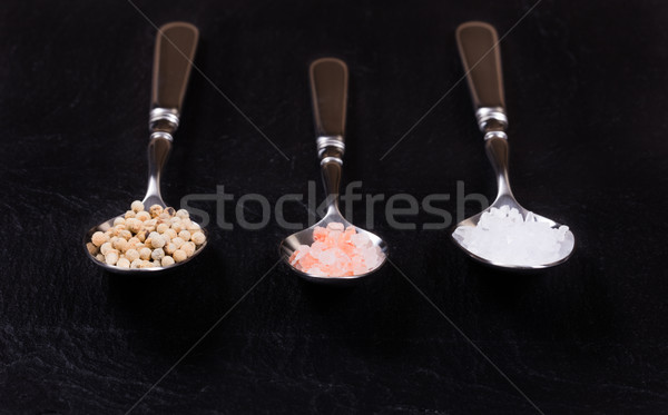 Spoons with a variety of spices on natural black slate stone  Stock photo © tab62