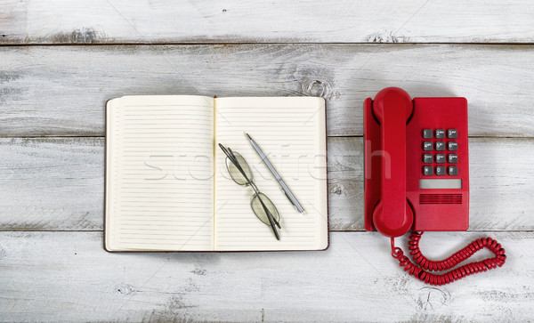 Vintage red phone and notepad with pen and reading glasses on ru Stock photo © tab62