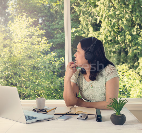woman working at home while looking out at bright daylight from  Stock photo © tab62
