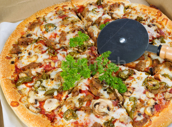 Large Pizza with cutter on top  Stock photo © tab62