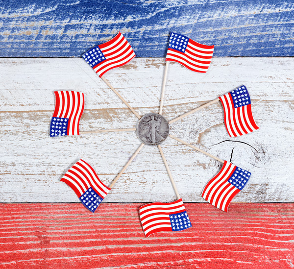 Small USA flags in circle formation around Liberty coin on rusti Stock photo © tab62