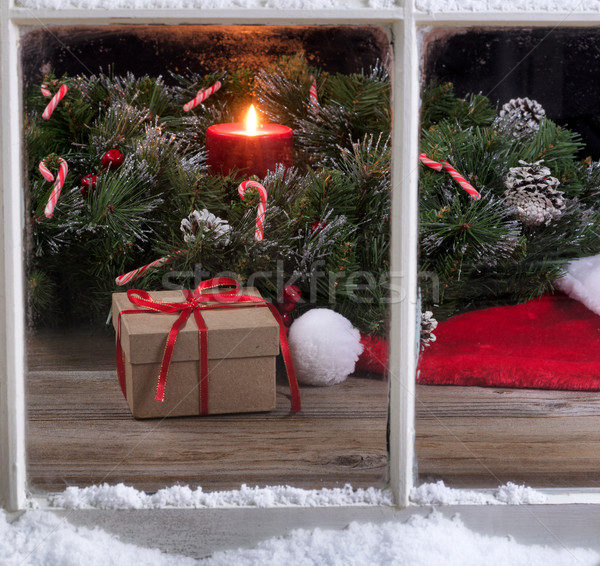 Snowy window view of gift box and Santa cap with burning candle  Stock photo © tab62