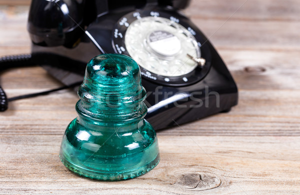 Antique glass insulator and rotary dial phone on rustic wooden b Stock photo © tab62