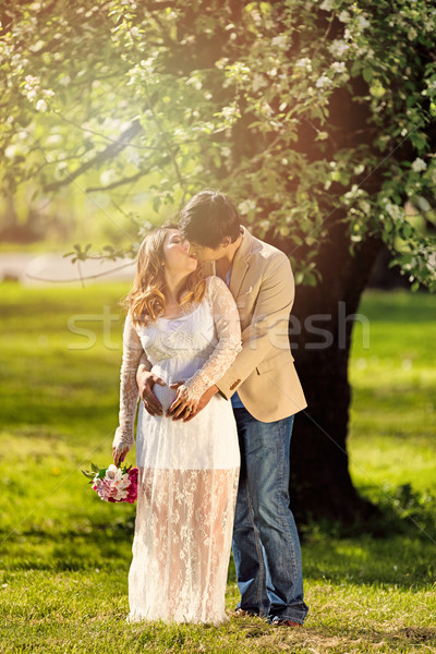 Expecting mom and dad kissing under flowering tree  Stock photo © tab62