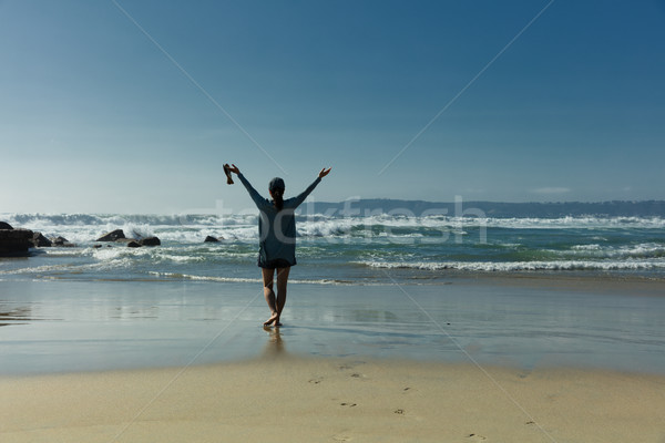 Woman walking towards ocean waves while barefoot     Stock photo © tab62