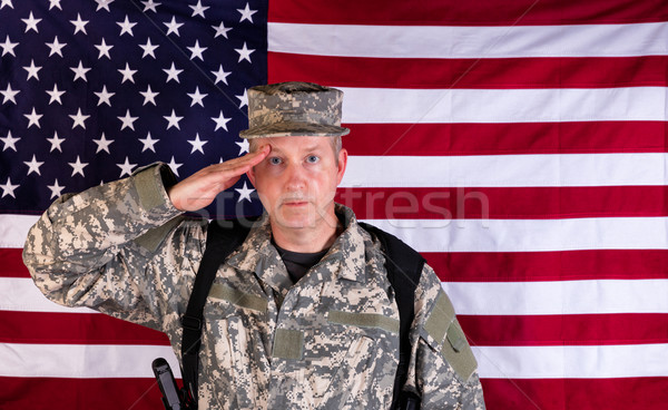 Male veteran solider saluting with USA flag in background while  Stock photo © tab62
