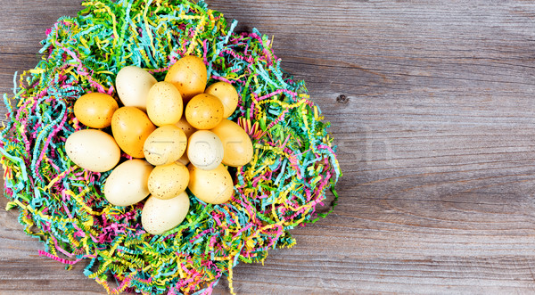 Easter eggs on top of colorful Mache paper with rustic wooden bo Stock photo © tab62