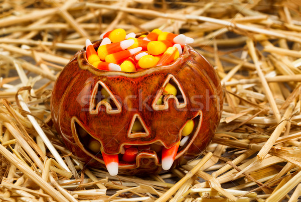 Spooky pumpkin filled with candy corn on straw Stock photo © tab62