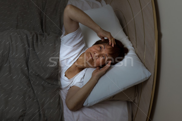 Restless senior woman staring at ceiling during nighttime while  Stock photo © tab62