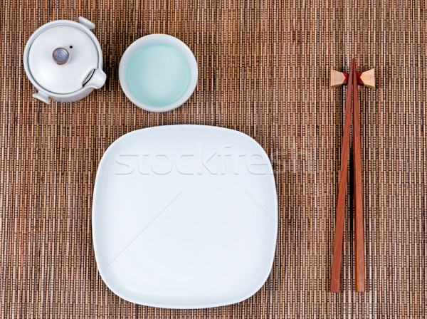 Bamboo mat with traditional Asian utensils plus white dinner pla Stock photo © tab62