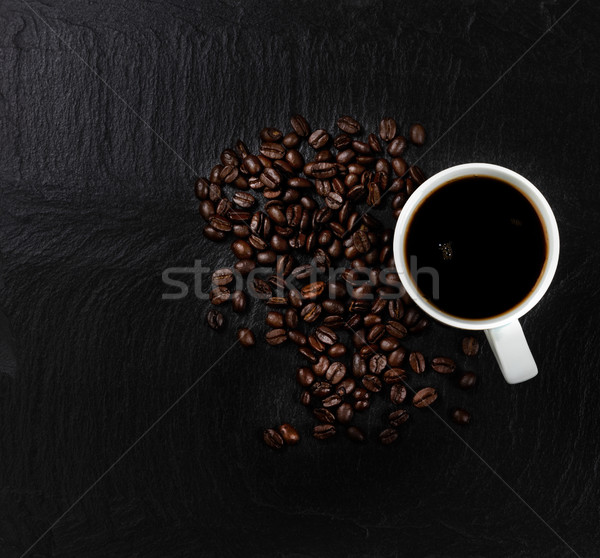 Dark coffee with roasted beans on natural slate stone background Stock photo © tab62