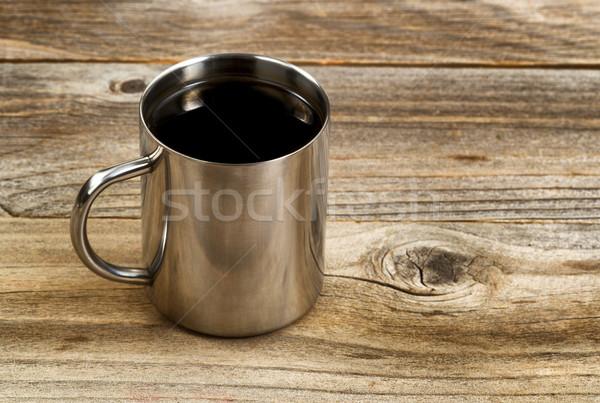 Fresh dark coffee in stainless steel cup on rustic wood Stock photo © tab62