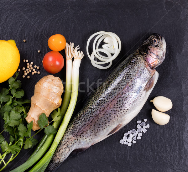 Fresh whole raw fish and herbs displayed on natural slate stone  Stock photo © tab62