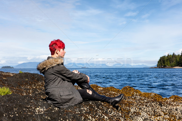 Teen girl thinking while sitting on rock near lake and woods Stock photo © tab62