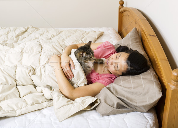 Mature woman looking at her cat while trying to sleep Stock photo © tab62