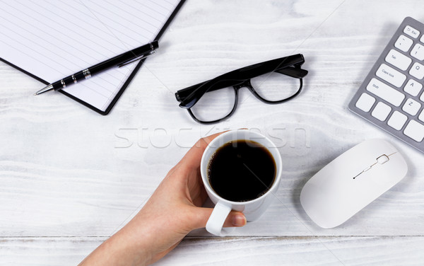 Female hand holding cup of coffee on organized white desktop  Stock photo © tab62