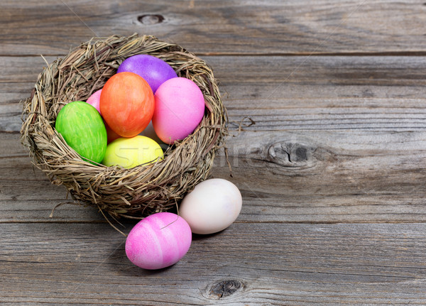 Close up front view of colorful Easter eggs in bird nest on rust Stock photo © tab62