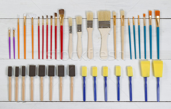 Organized new paintbrushes and applicators on white wooden board Stock photo © tab62