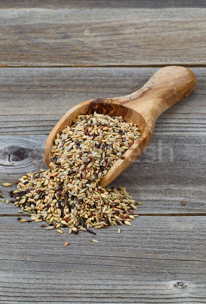 Raw rice in wooden scoop spilling onto rustic wood Stock photo © tab62