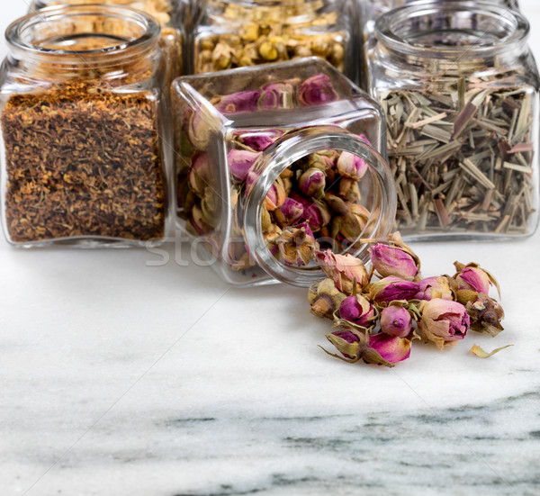 Spices and herbs in small glass jars pouring onto white marble s Stock photo © tab62