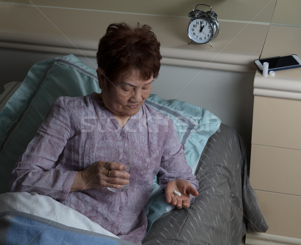 Senior woman taking medicine with water while lying in bed Stock photo © tab62