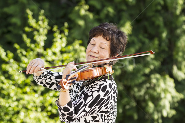 Senior woman concentrating while playing music outdoors  Stock photo © tab62