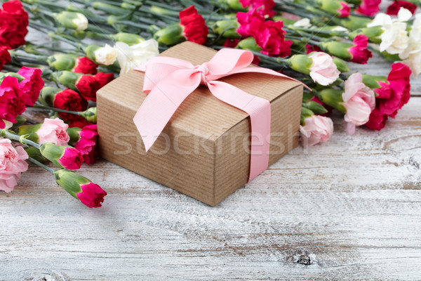 Stock photo: Gift box with carnation flowers in background on white weathered