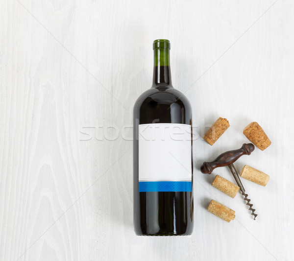 Large bottle of red wine with an antique corkscrew and old corks Stock photo © tab62