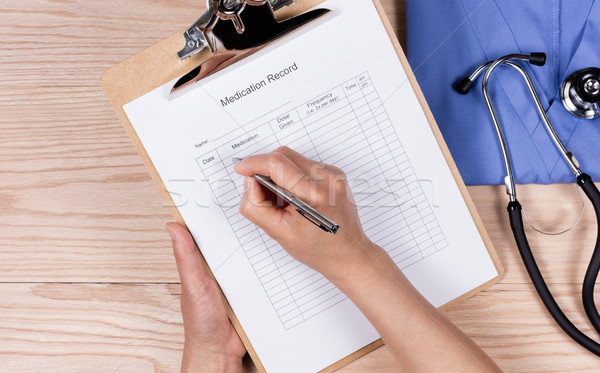 Doctor working on patient medication form with medical objects o Stock photo © tab62