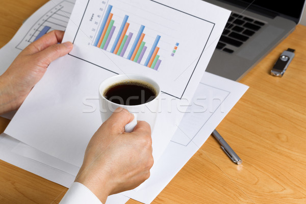 Female hand holding a cup of coffee while reviewing financial ch Stock photo © tab62