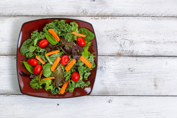 Healthy green salad in dark plate with rustic white wooden board Stock photo © tab62