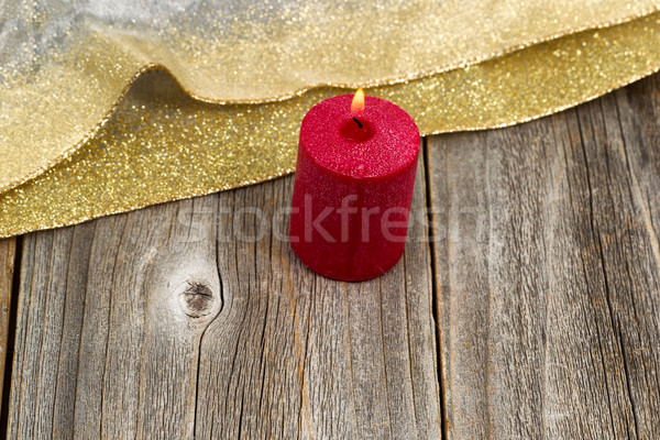 Burning candle with gold colored ribbon on rustic wooden boards Stock photo © tab62