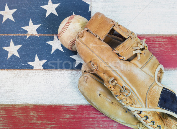 Old worn baseball mitt and ball on faded boards painted in Ameri Stock photo © tab62