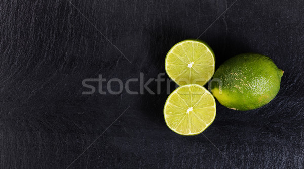 Overhead view of organic limes on black slate background  Stock photo © tab62