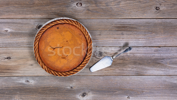 Stock photo: Freshly baked pumpkin pie with spatula on rustic wooden table